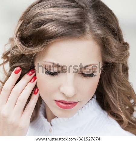 Beautiful young romantic elegant woman face, has closed eyes, haired nature hair, long eyelashes, hand with red manicure, sexy lips. Pure makeup. White blouse.   - stock photo