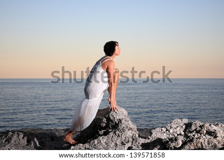 beautiful young russian woman on a white dress by the sea - stock photo