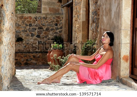 beautiful young russian woman with long pink dress on the street of traditional place - stock photo
