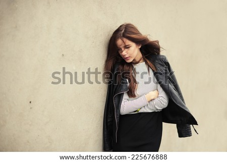 Beautiful young sad girl on a background of a wall on a windy day