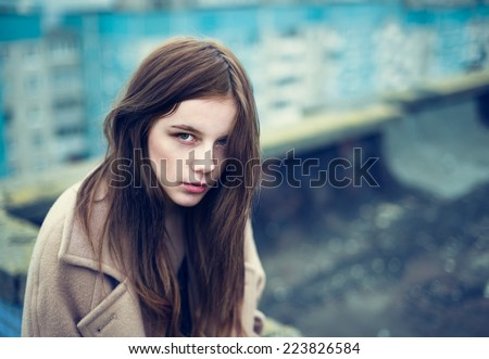 Beautiful young sad girl on the roof of a cold autumn. Photo in cold tones - stock photo