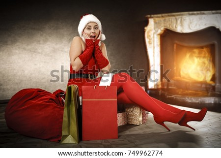 Beautiful young santa claus woman sitting on a gift bag from Santa Claus. The interior of the room with a large old fireplace and burning. A place for your advertising or a slogan.
