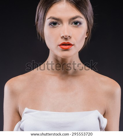Beautiful young seductive woman standing over dark background. Front view. - stock photo