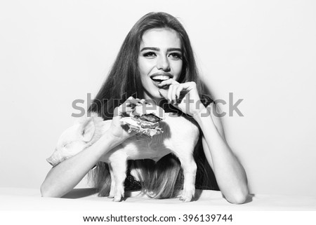 Beautiful young sensual happy smiling woman and cute pink small pig pet in cloth eating tasty big fresh burger on studio background black and white, horizontal picture