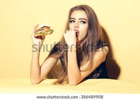 Beautiful young sensual woman eating tasty big fresh burger indoor on studio yellow background, horizontal picture - stock photo