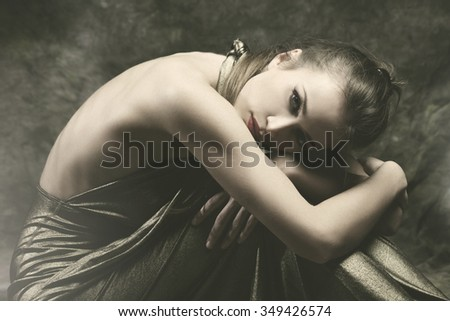 beautiful young sensual woman in elegant dress sit with wrap  arms around legs,  studio shot, small amount of grain added