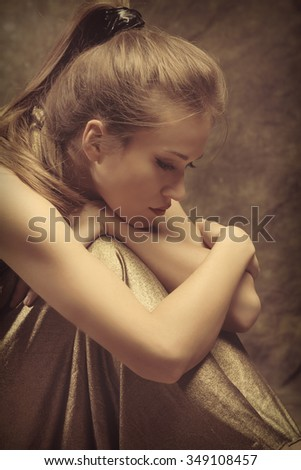 beautiful young sensual woman in golden dress sit with wrap  arms around legs, side view, studio shot