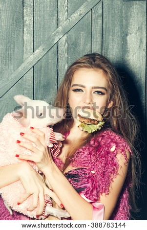Beautiful young sensual woman in stylish fur waist coat holding cute pink small pig pet in cloth and tasty big burger in hands on wooden background, vertical picture