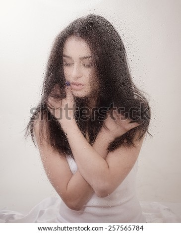 Beautiful young sensual woman is in bed on white sheet behind wet window, image toned. - stock photo
