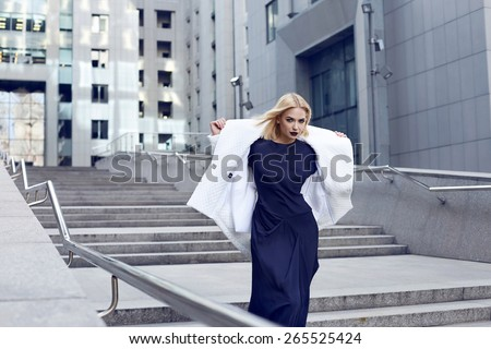 Beautiful young sexy blonde attractive woman with a hairstyle and bright evening make-up dressed in stylish fashion designer clothes Cocktail dress high heels at the party  walking on the street  - stock photo