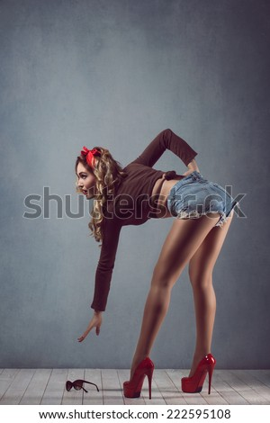 Beautiful young sexy blonde slim figure with a red armband with red lips in denim shorts in red high heels with long legs wearing glasses Pin Up dropped glasses ass - stock photo