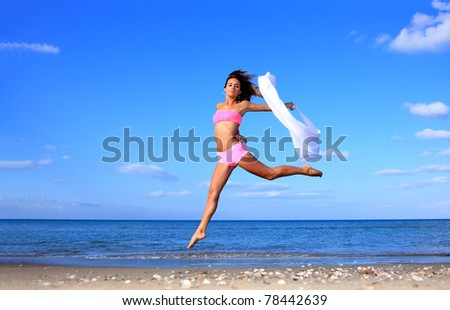 Beautiful young sexy Brazilian model jumping by the sea - stock photo