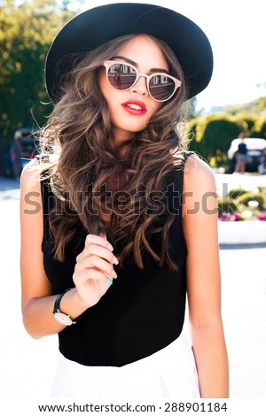 Beautiful young sexy brunette girl with long curly hair with bright evening make-up,wearing a slinky silk dress high heels a little bag necklace,wealth and luxury,party background baroque.Street style - stock photo