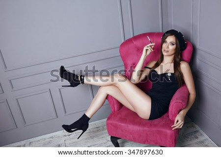 Beautiful young sexy brunette woman in black beret and a short silk dress smokes a cigarette sitting in pink armchair stylish clothes trendy shoes fashion makeup hair long legs tanned skin body shape