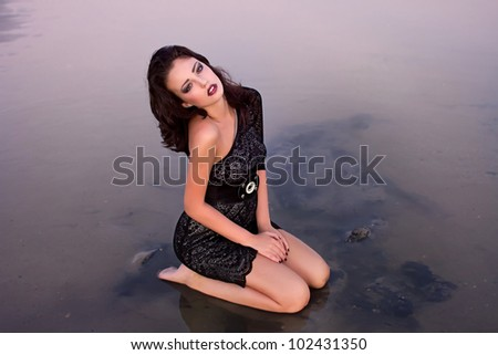 Beautiful young sexy fashion model in dress in  the sea - stock photo