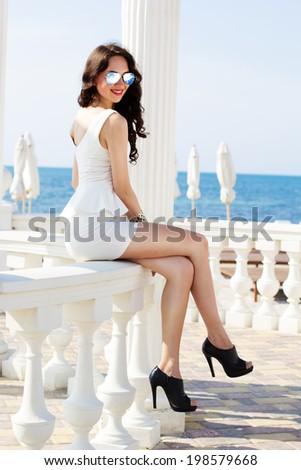 Beautiful young sexy fashion model posing near the sea - stock photo