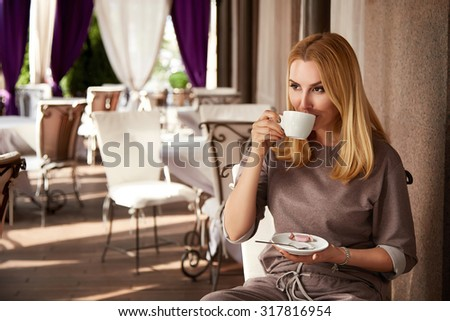 Beautiful young sexy girl blond woman with makeup and hairstyle sitting cafe restaurant bar drinking cappuccino latte tea interior summer terrace sun shade summer day relaxing breakfast meeting date