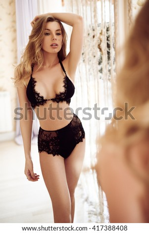 Beautiful young sexy girl in lingerie looking at herself in the bathroom mirror - stock photo