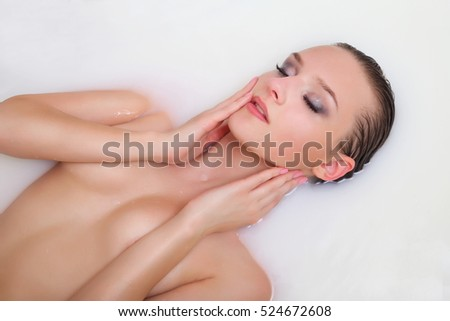 Beautiful young sexy girl portrait in milk