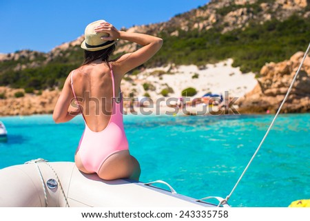 Beautiful young sexy girl relaxing on the boat in open sea - stock photo