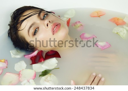 Beautiful young sexy girl with dark hair wet, evening makeup, takes bath with milk tan perfect  skin in romantic atmosphere, beauty cosmetic salon and spa for woman at Valentine's Day - stock photo