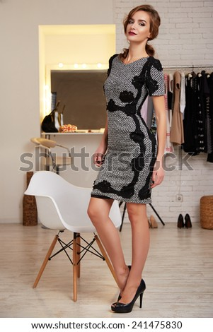Beautiful young sexy girl with long wavy blond hair with a bright evening make-up perfect summer tan thin figure wearing a short evening cocktail dress and high heel shoes in the interior of the shop - stock photo