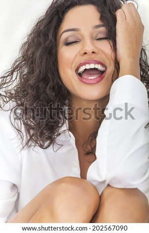 Beautiful young sexy happy Latina Hispanic woman with perfect teeth open mouthed laughing in ecstasy - stock photo