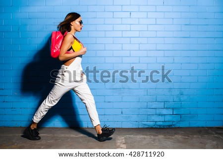Beautiful young sexy hipster girl goes near urban blue wall background in yellow swimsuit, white jumpsuit, sneakers, sunglasses, pink backpack. - stock photo