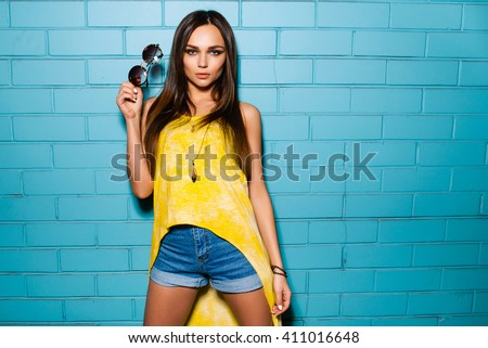 Beautiful young sexy hipster girl posing and smiling near urban blue wall background in yellow dress, shorts, shirt, sneakers, sunglasses. - stock photo