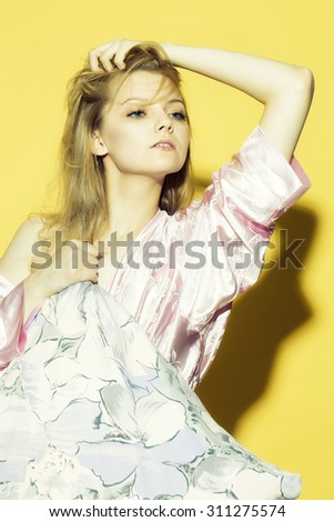 Beautiful young sexy pensive woman with blonde hair in satin pink dressing gown in soft flower pattern holding pillow in bright pillow-case pastel colours on yellow studio background, vertical picture - stock photo