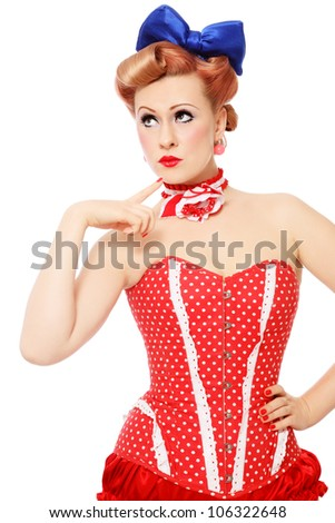 Beautiful young sexy pin-up promo girl in polka dot corset looking upwards with thoughtful expression, on white background