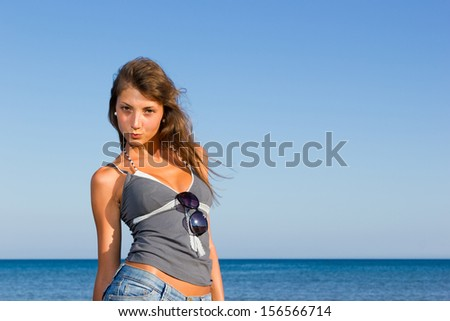 Beautiful young sexy woman in jeans shorts on the beach