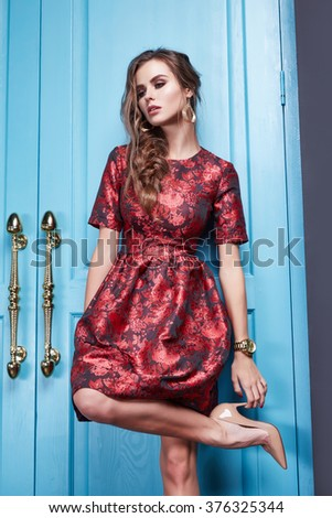 Beautiful young sexy woman in smart evening dress red silk dress new stylish fashion collection autumn winter season, long brown hair, shoes, interior blue door in the bedroom room - stock photo