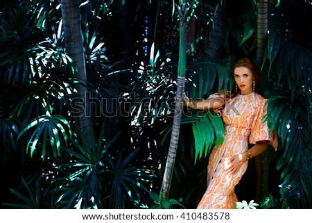 Beautiful young sexy woman model with perfect figure, bright makeup, wearing orange dress with python pattern, in palm leaves in the jungle, shadows, shining sun, free place for text. Fashion photo - stock photo