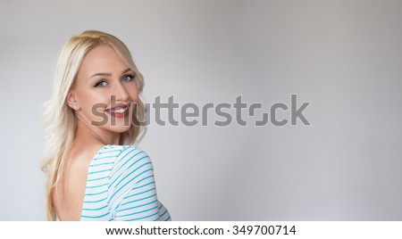Beautiful young sexy woman posing against a white wall - stock photo