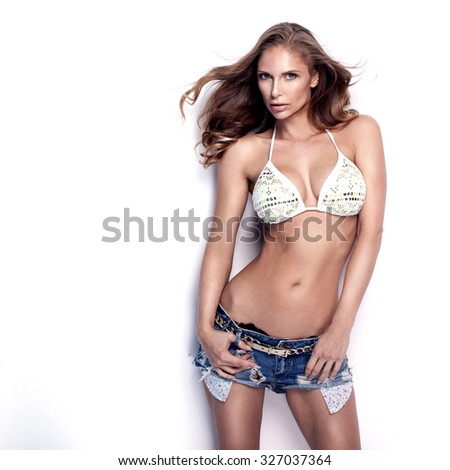 Beautiful young sexy woman posing in short jeans and swimwear, looking at camera. Studio shot. White background. - stock photo