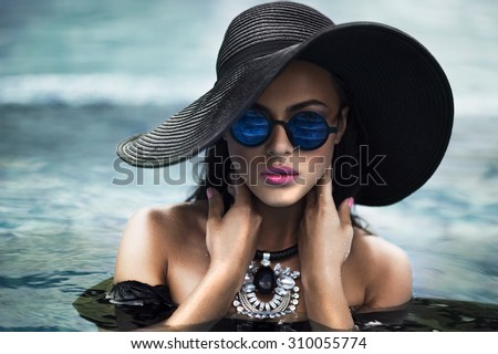 Beautiful young  sexy woman posing on a pool. Fashion style. - stock photo