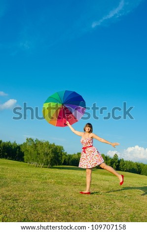 Beautiful young sexy woman posing on nature with color umbrella