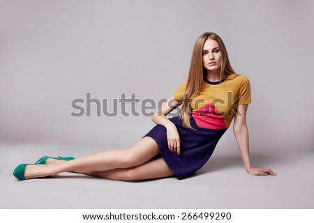 Beautiful young sexy woman with long blonde hair with natural make-up wearing short evening dress for party sitting on the floor model with a clothing catalog spring collection fashion style  - stock photo