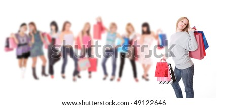 Beautiful young shopping woman with girls holding bags on background