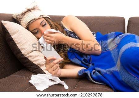 Beautiful young sick girl lying down with a cold blowing her nose and checking  her phone
