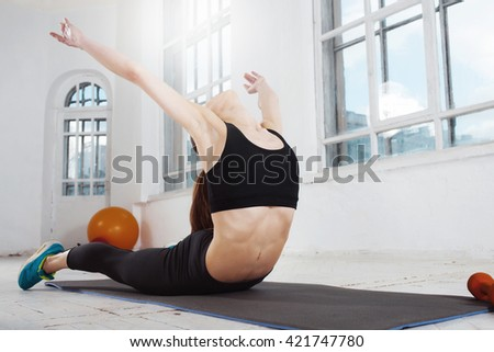 Beautiful young slim woman  doing some gymnastics at the gym