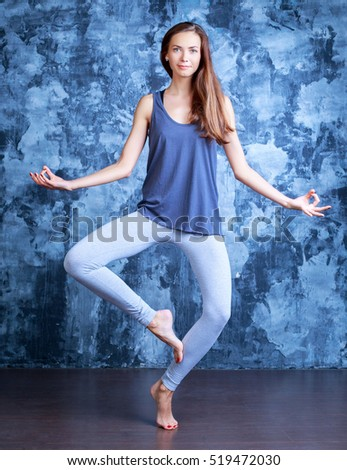 beautiful young slim woman doing yoga against studio background