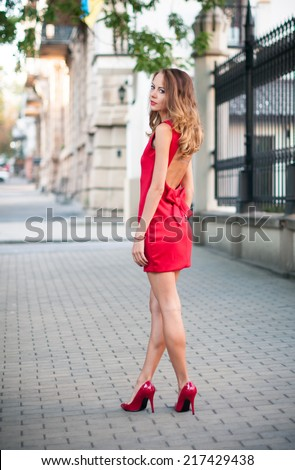 Beautiful young slim woman in a street of European city, business lady in red dress and high heels. - stock photo