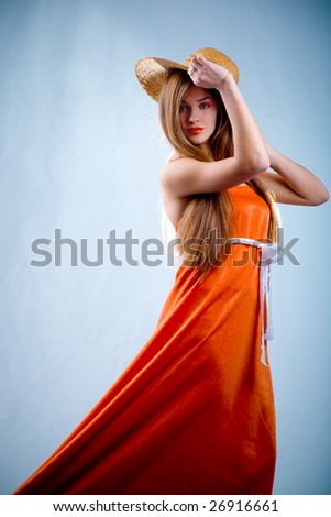 Beautiful young slim woman in long orange dress and straw on blue background - stock photo