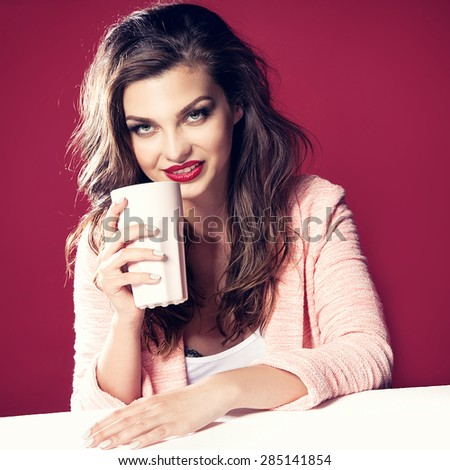 Beautiful young smiling brunette woman holding cup of tea or coffee. Girl looking at camera.  - stock photo