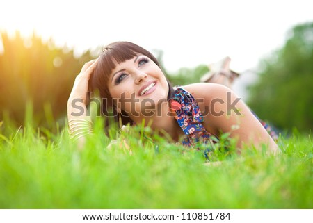 beautiful young smiling brunette woman in park relaxing on green grass at warm autumn day.alluring happy girl in colorful dress resting and dreaming on meadow outdoor.Romantic lady on nature at sunset