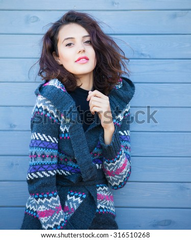 Beautiful young smiling brunette woman with  wearing knitted nordic print cardigan on a grey wooden background. Winter fall fashion concept. - stock photo