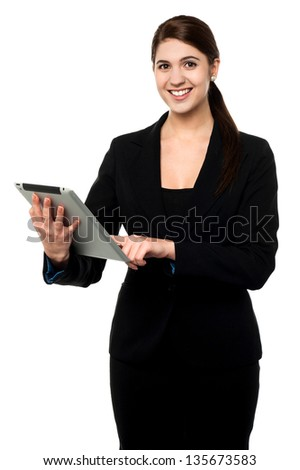 Beautiful young smiling businesswoman working on touch pad.