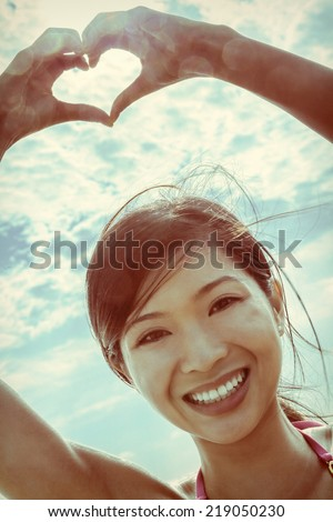 Beautiful young smiling Chinese Asian woman girl on a beach in a bikini, making a hand heart shaped finger frame. Photograph processed with an Instagram vintage style filter - stock photo